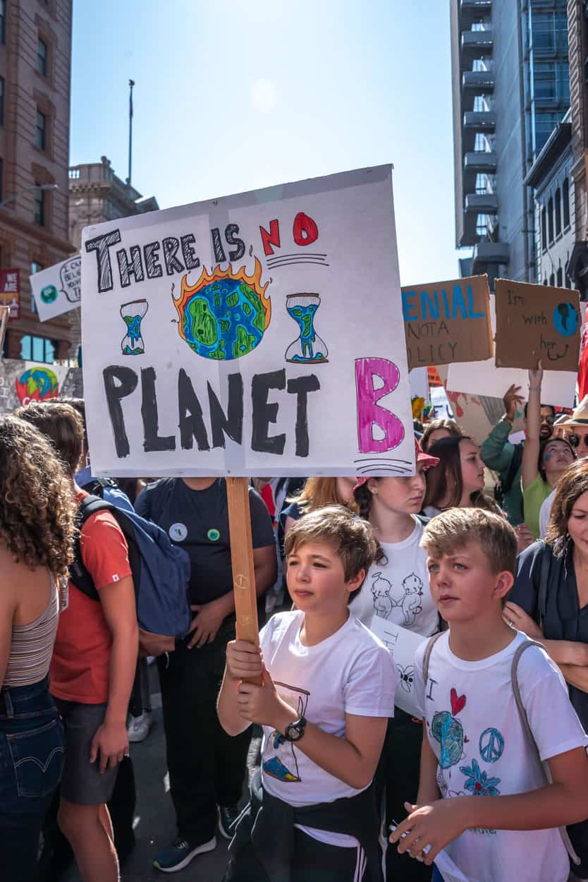 """Boys stand together holding a sign reading, """"There is no Planet B"""""""