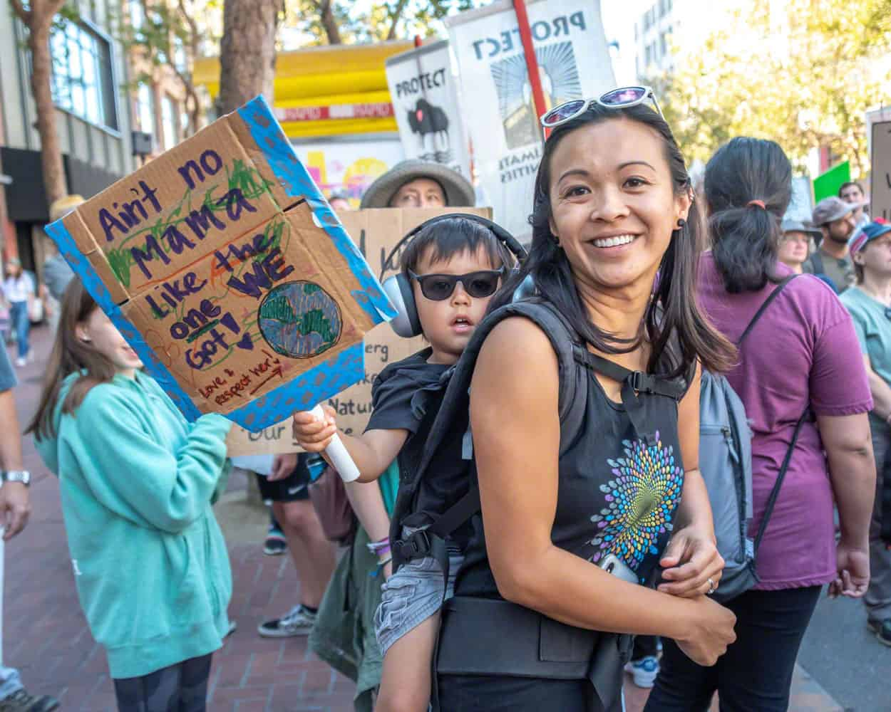 A mother carries a small child on her back at the Climate Strike March