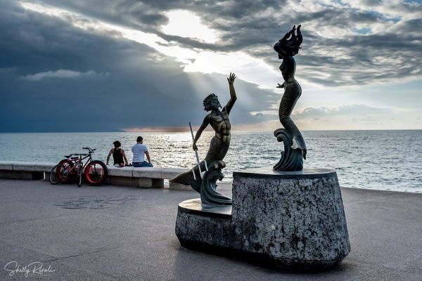 friends visit beside Triton and Mermaid sculpture on the Malecon