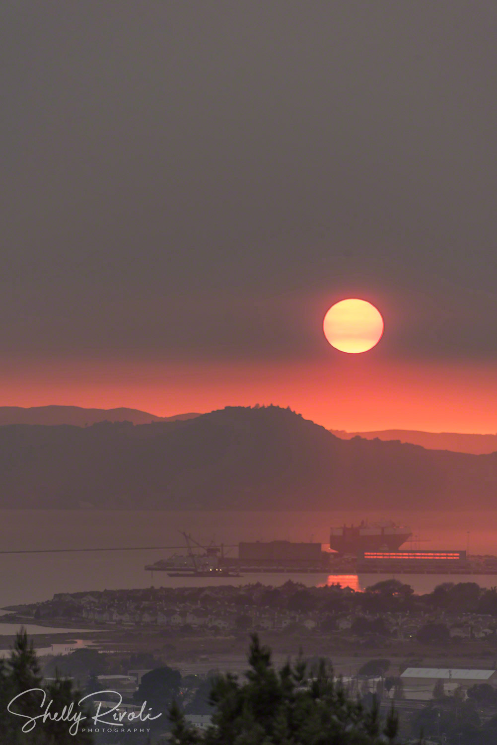 The setting sun sinks into a blood red band over the Marin Headlands and Point Richmond, California.