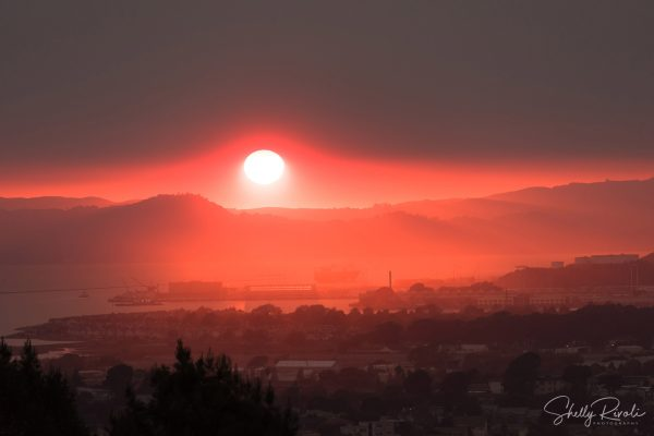red sunset over San Francisco Bay caused by wildfire smoke